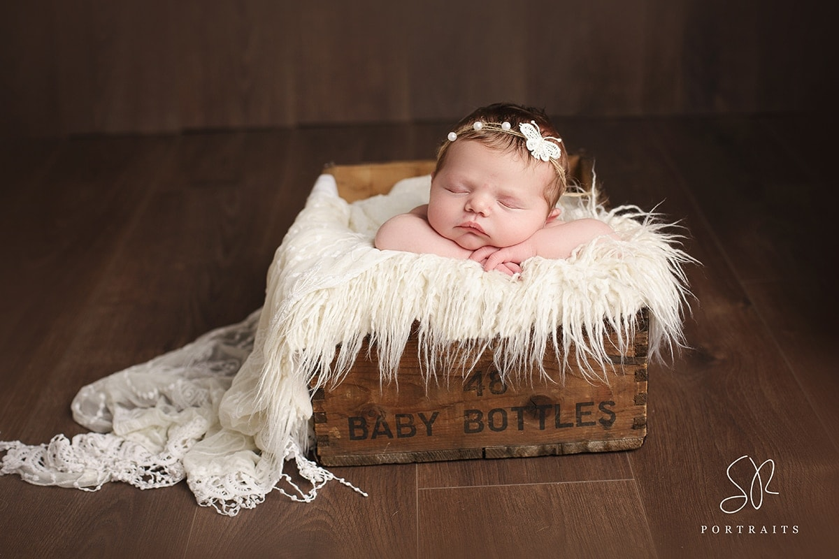 Newborn Photographer SR Portraits Leicester wood photos- baby in wood crate with white butterfly headband