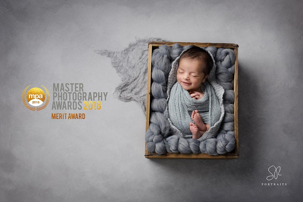 award winning image smiling baby on grey background SR Portraits newborn photography Leicestershire