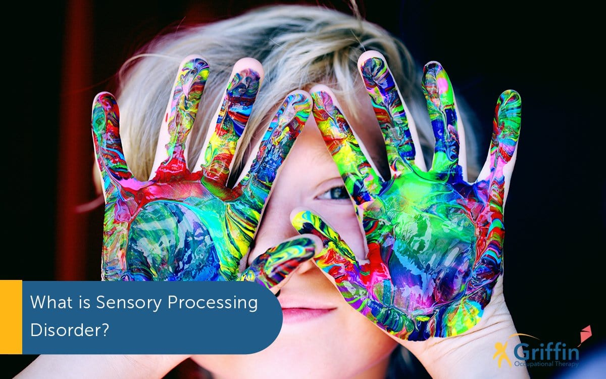 boy with coloured paint on hands text what is sensory processing disorder
