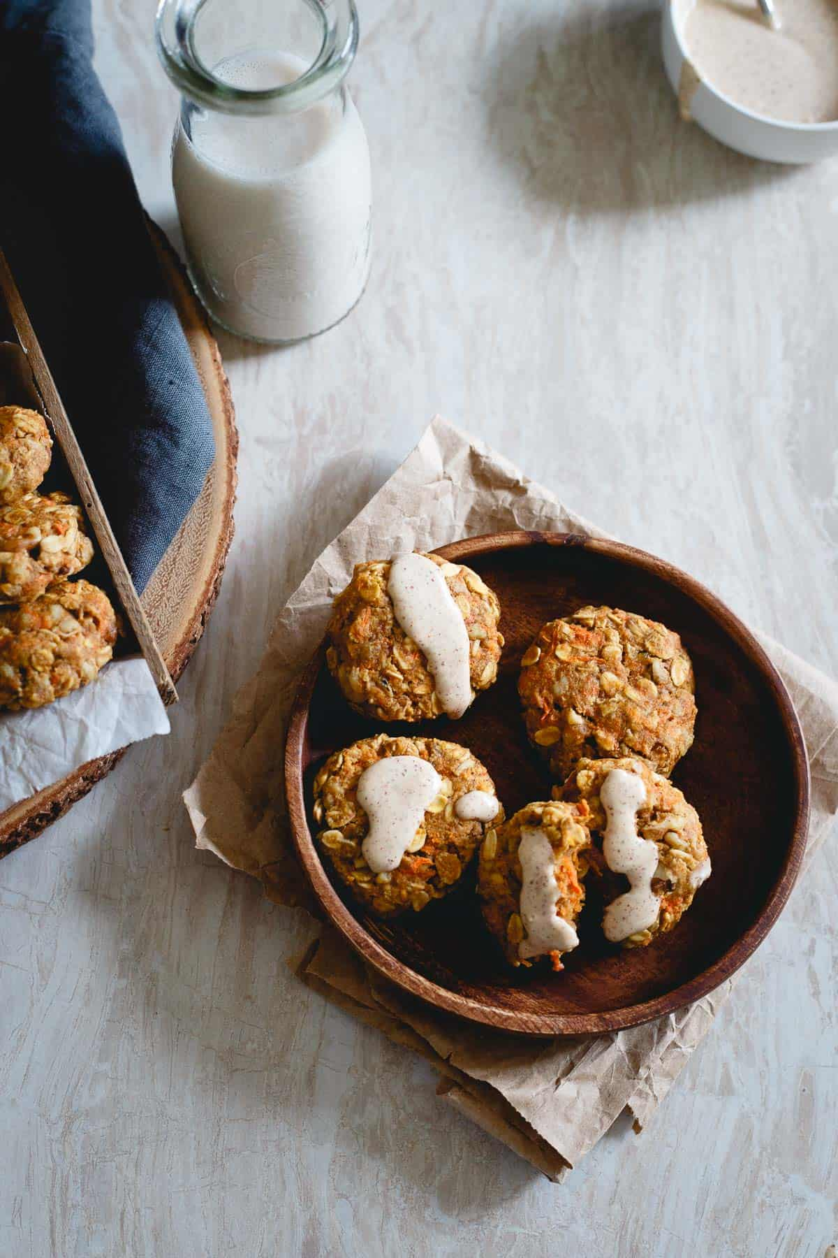 Real carrots, raisins, ginger, lemon zest and walnuts are packed into these healthy carrot cake cookies drizzled with a cream cheese almond butter icing.