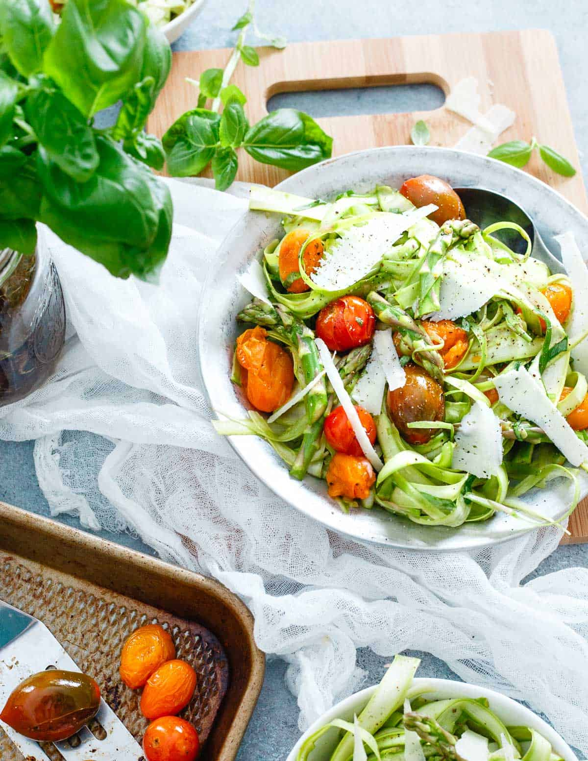 Thinly shaved asparagus makes a delicious spring salad when combined with roasted tomatoes, basil and lots of bright lemon!