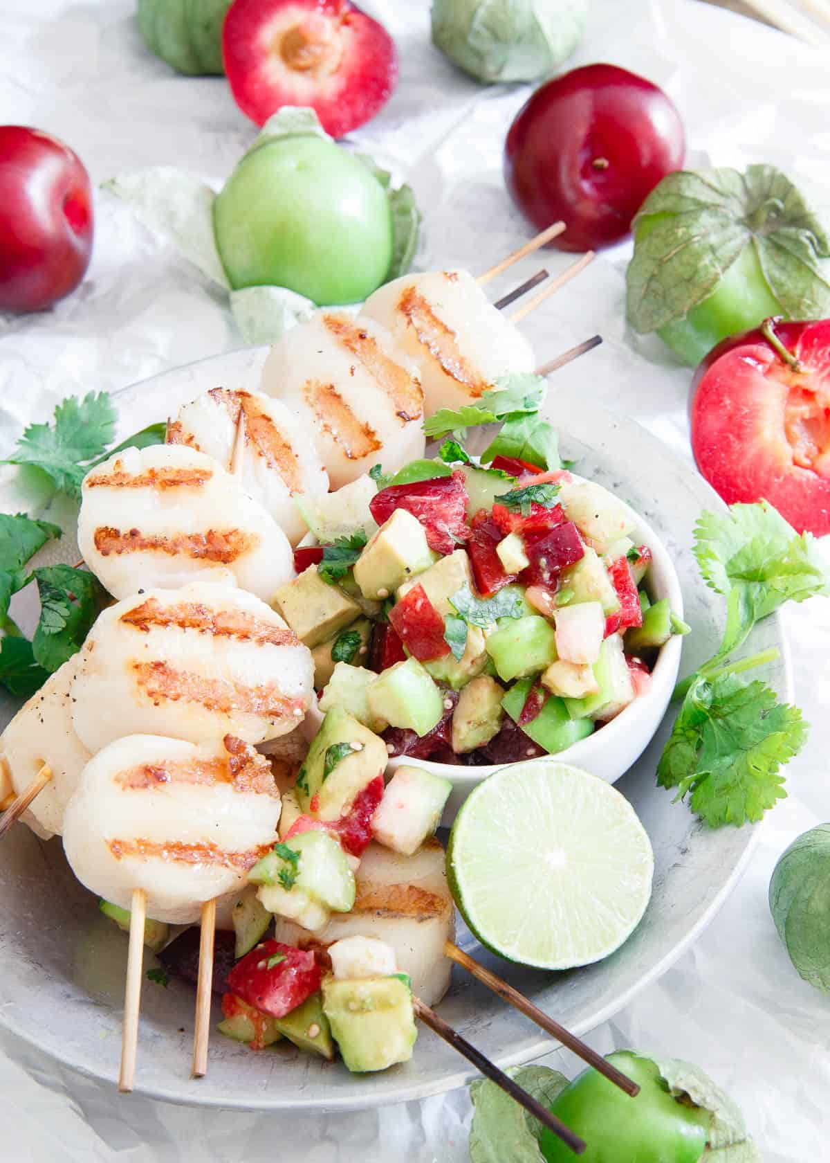 These grilled scallops are simply prepared and topped with a fresh summery tomatillo plum salsa for a delicious light meal.