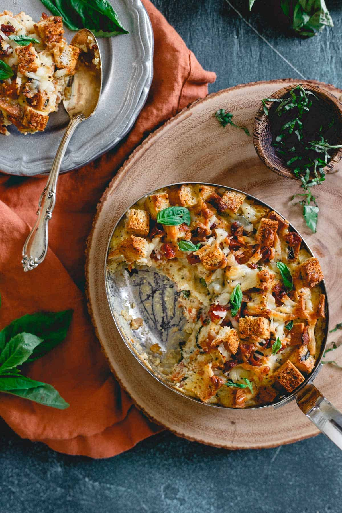 Everything bagels are used in this breakfast strata combined with bacon, cheese, basil and sun-dried tomatoes for a delicious gluten-free brunch.