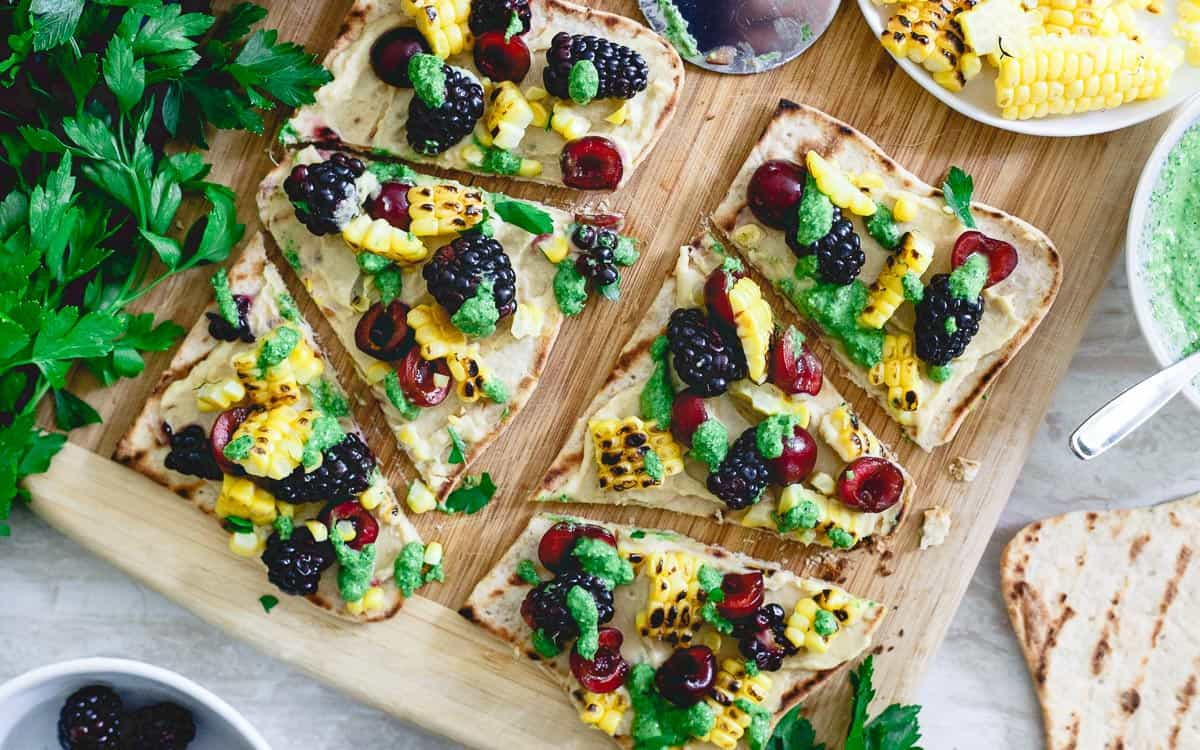 This hummus flatbread is a pre-dinner snack bursting with summer flavors from grilled corn to berries, cherries and fresh parsley pesto.