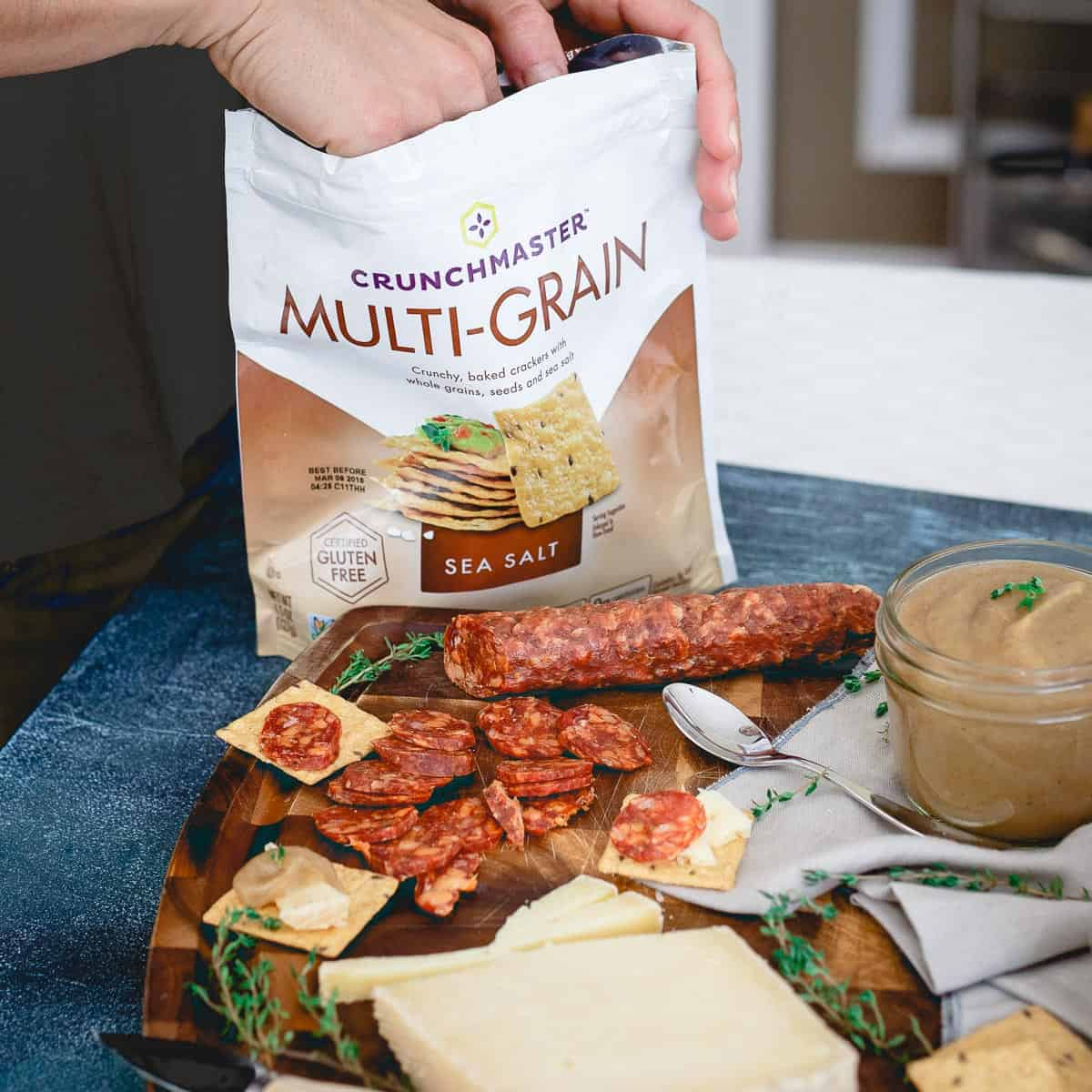 Crunchmaster multi-grain crackers are the perfect addition to a cheese, charcuterie and pear apple butter spread.
