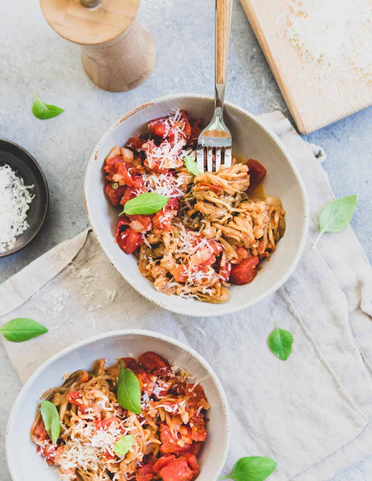 Eggplant noodles are tossed with a fresh chunky tomato basil sauce and topped with parmesan cheese.