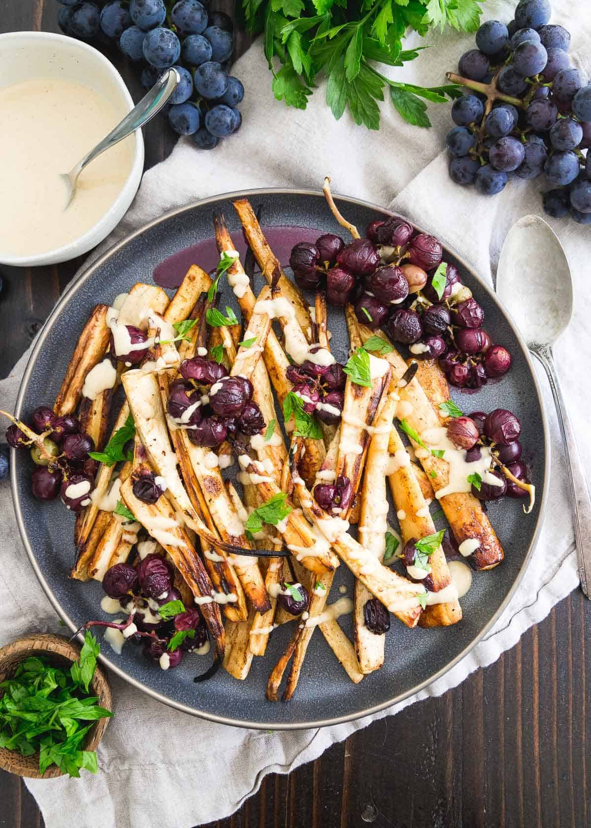 These roasted parsnips with cinnamon and brown sugar are the perfect holiday side dish. Roasted grapes and a sweet hummus drizzle make it a dish to remember!