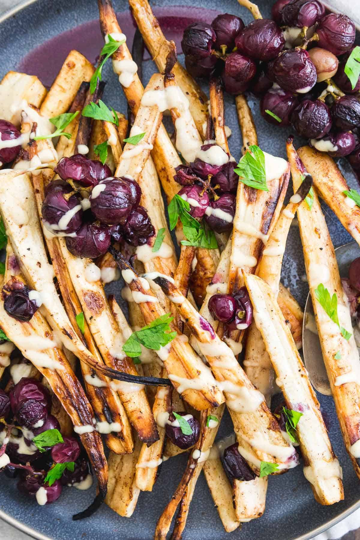 Cinnamon sugar roasted parsnips with concord grapes and a sweet maple hummus drizzle make a delicious and impressive holiday side dish.