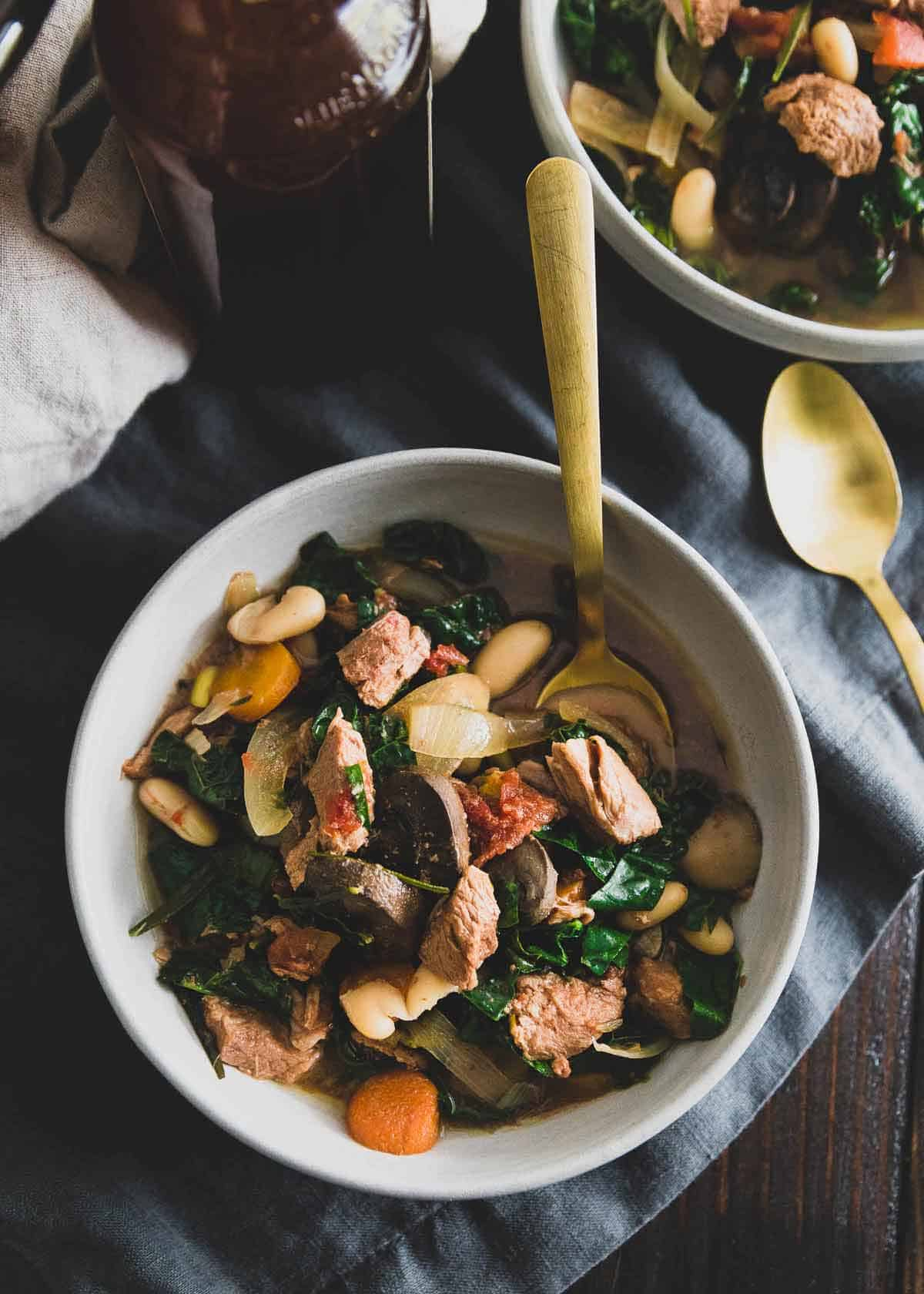 This slow cooker lamb stew is a hearty, cozy bowl of comfort made with lean American lamb stew meat, mushrooms, white beans, kale, tomatoes and rosemary.
