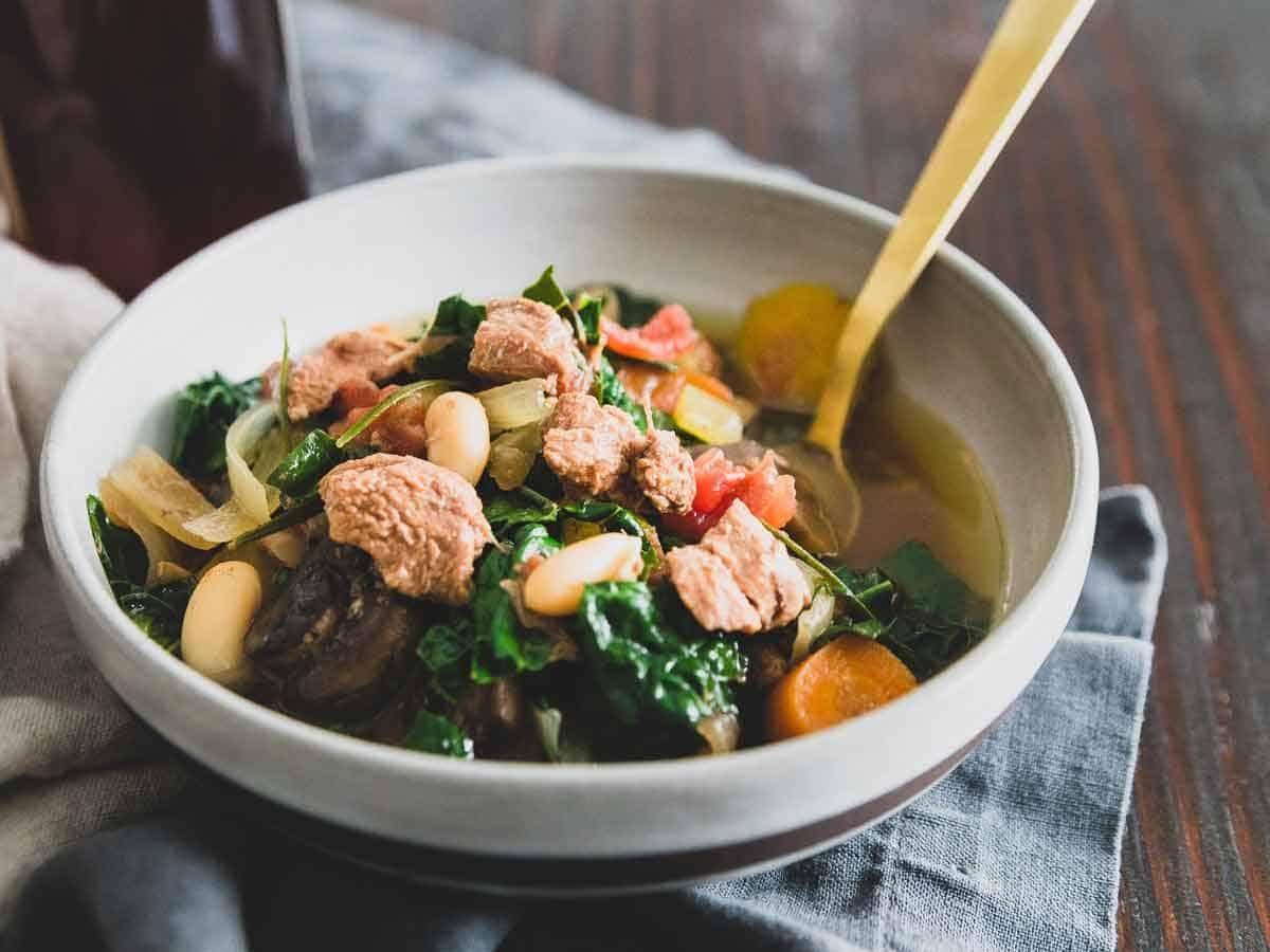 A lamb stew slow cooker recipe with hearty white beans, mushrooms, kale, tomatoes and carrots flavored with fresh rosemary.
