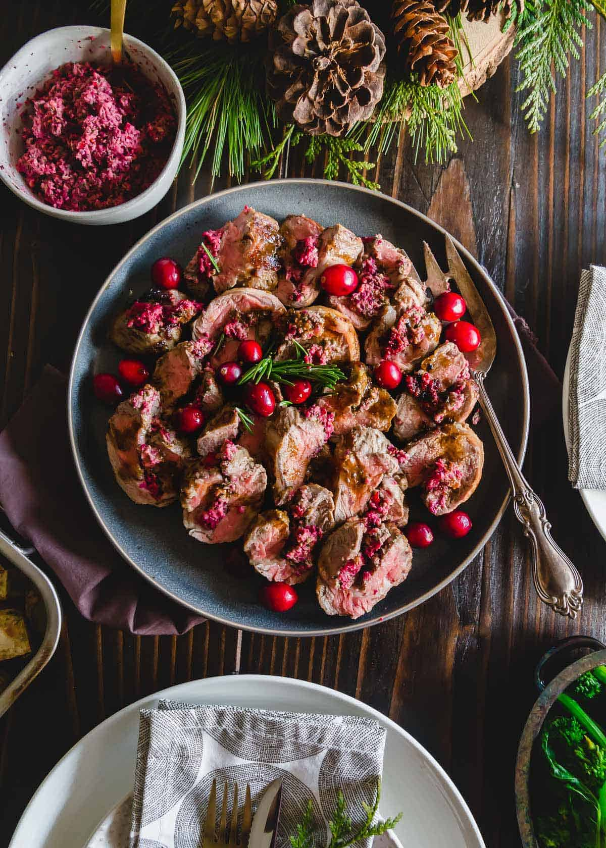 A simple cranberry pesto made with basil, mint, garlic and pine nuts makes this stuffed American lamb recipe a gorgeously festive and delicious winter dish perfect as a holiday dinner party centerpiece.