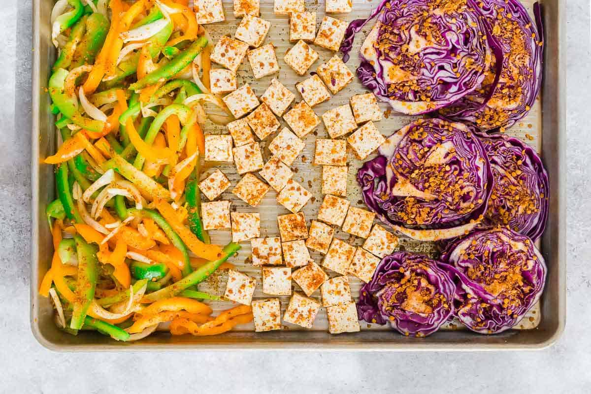 Sheet pan roasted tofu, red cabbage and mixed bell peppers and onions make an easy plant based meal prep option.