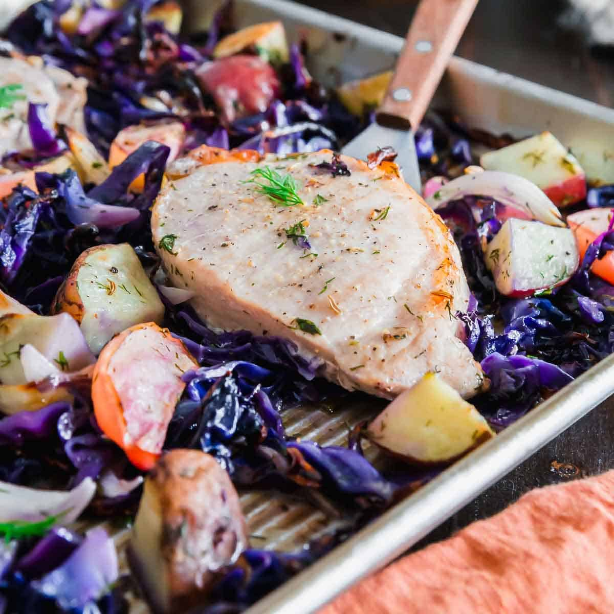 Cooking pork chops on a baking sheet along with all the sides at one time is the easiest way to make a complete dinner in no time.