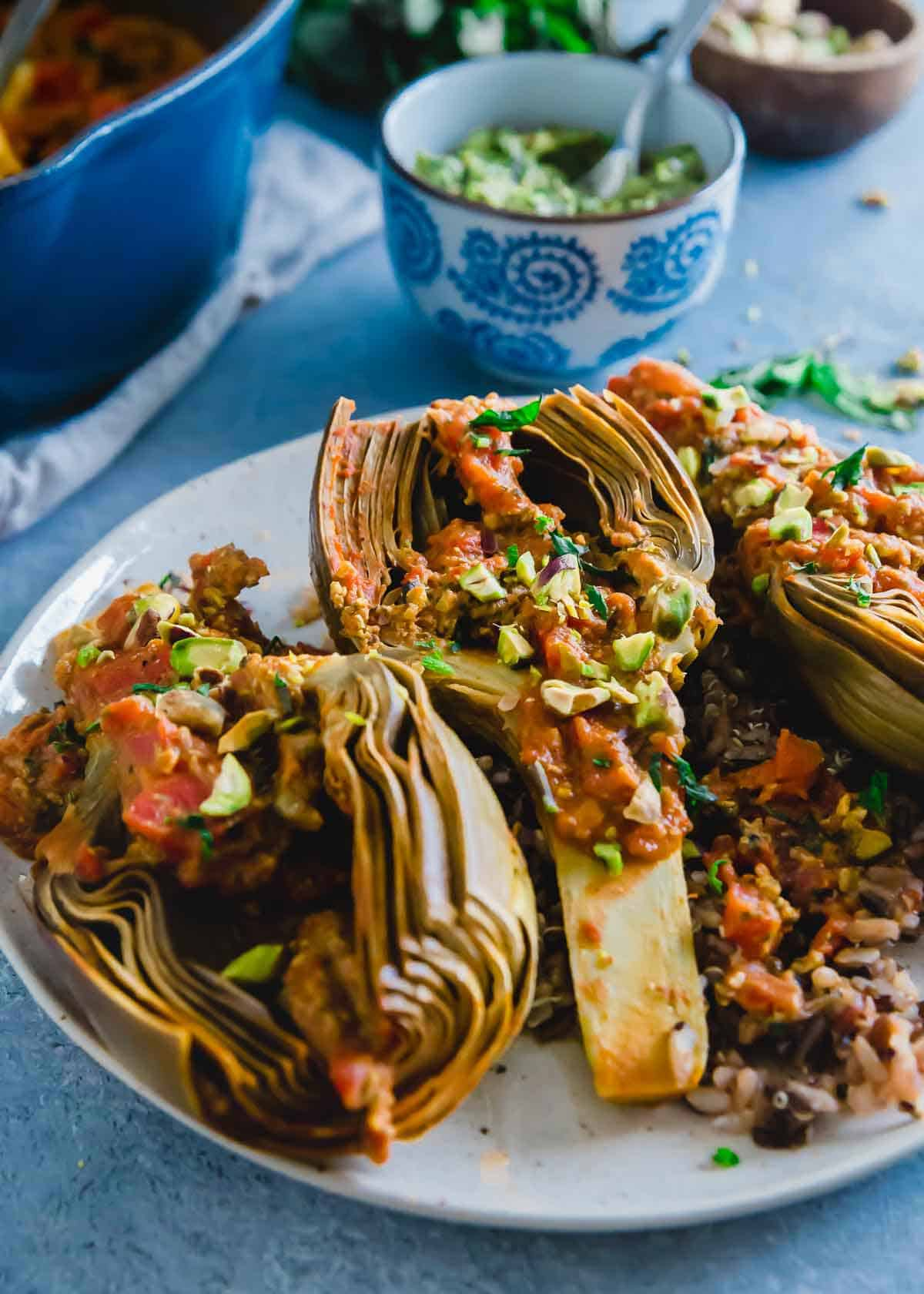 Simple tomato braised artichokes cooked until tender and served with a pistachio basil pesto.