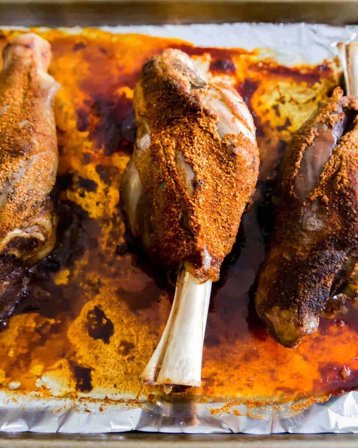 After baking, these BBQ lamb shanks are slathered in BBQ sauce and then finished on the grill.