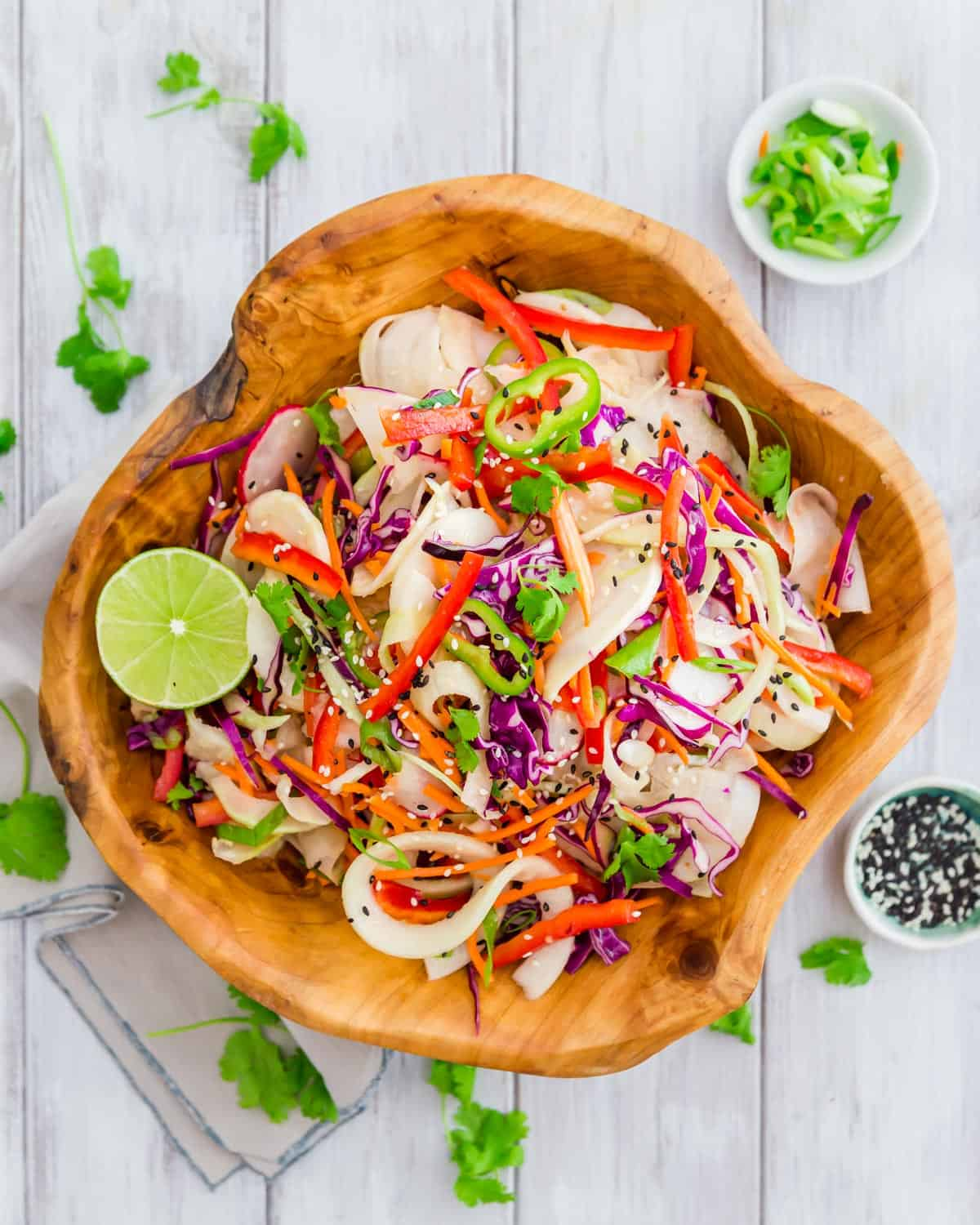 A colorful, easy salad with kohlrabi noodles, red cabbage, red pepper, carrots, radishes and green onion all tossed with a Thai inspired vinaigrette.