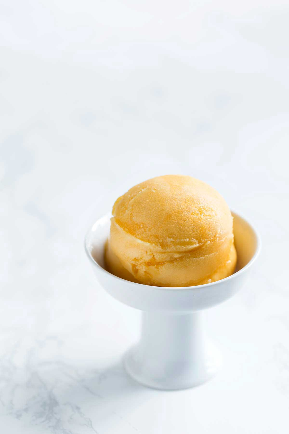 Passion fruit sorbet in a white bowl on a marble backdrop.