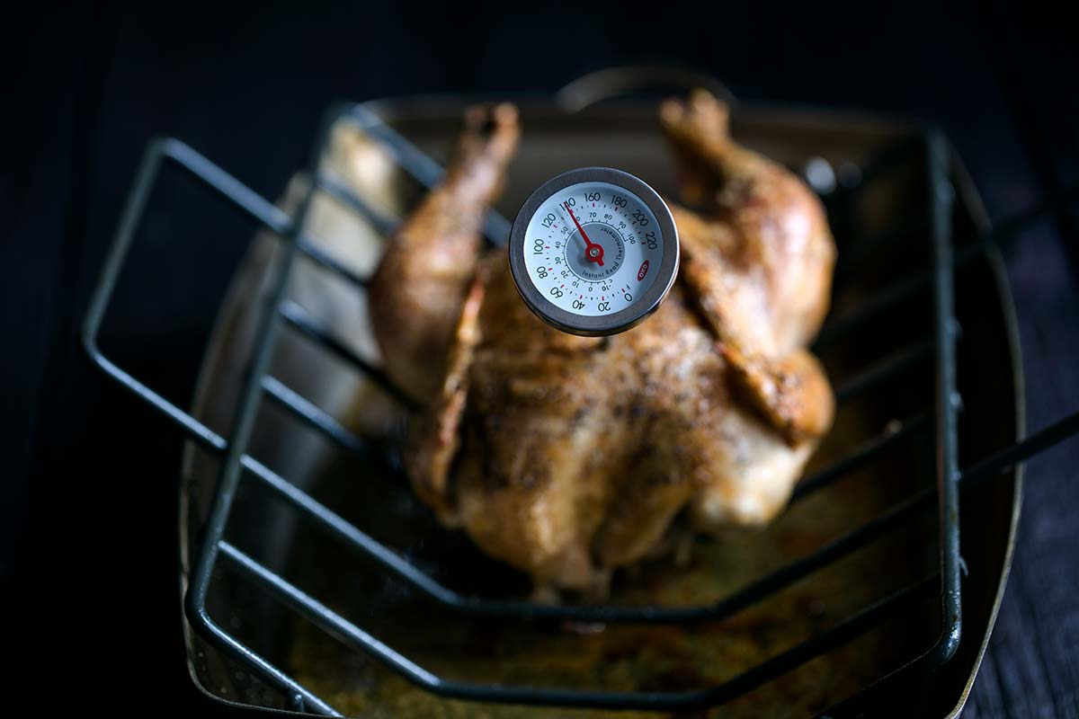 A roasting pan with a whole roasted chicken and a thermometer