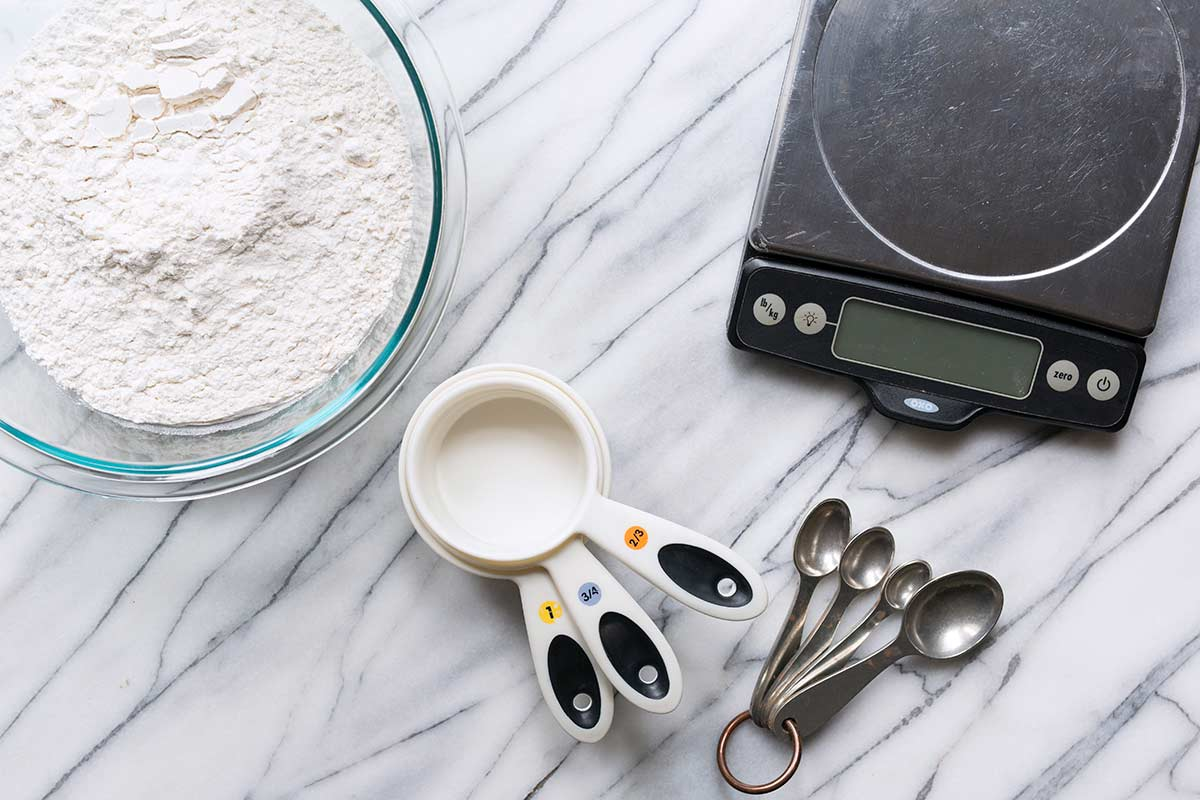 Measuring cups, spoons, a digital scale, and a bowl of flour.