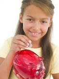 Young girl putting coin into piggy bank smiling