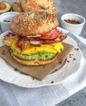 Bacon Egg and Avocado Breakfast Bagel - an easy, filling and flavorful breakfast! Made with fluffy, scrambled eggs, sliced tomato, bacon, cream cheese, and a delicious garlic avocado mash - all sandwiched between an everything bagel. Breakfast has been perfected! #breakfast #bagel #breakfastbagel