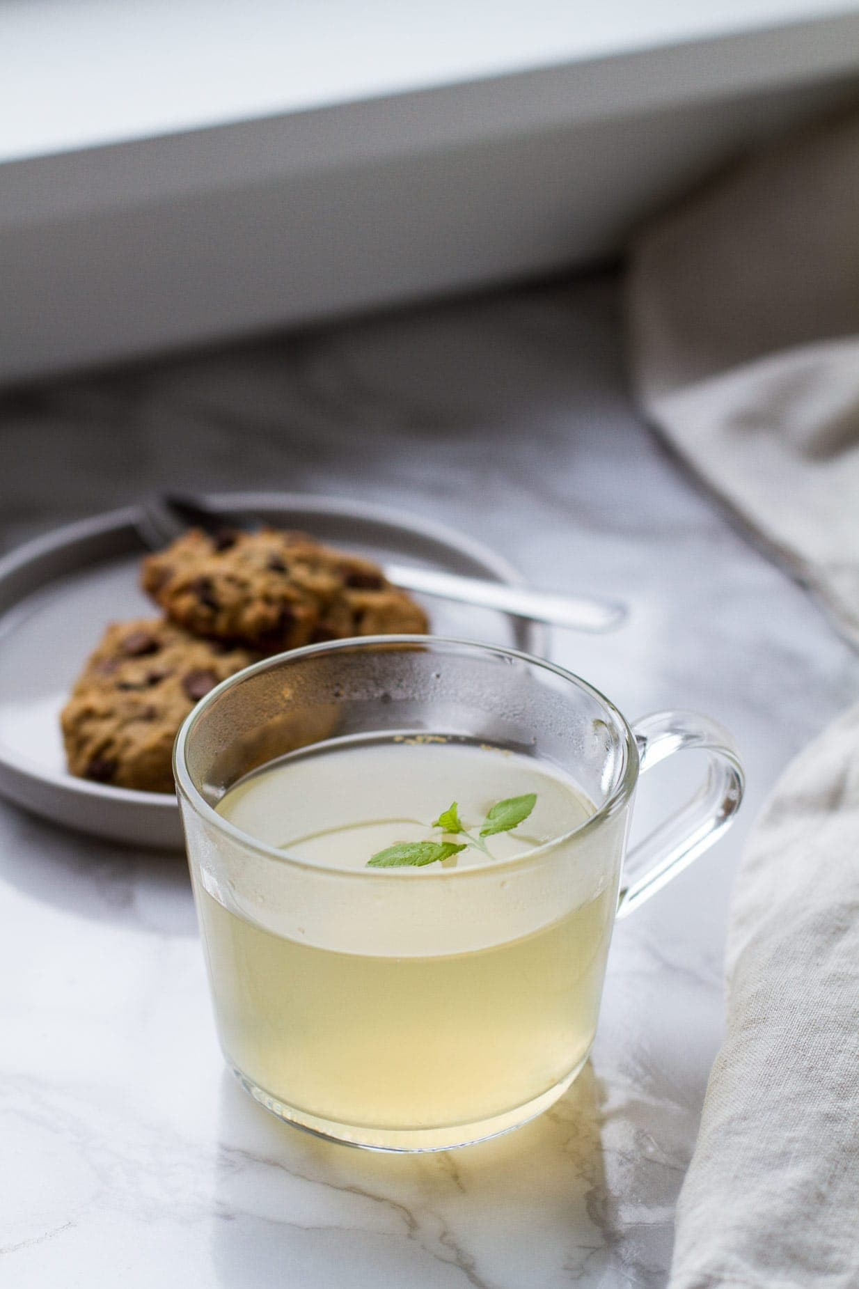 Clear mug with pale yellow drink and lemon verbena garnish. Cookies in the background.