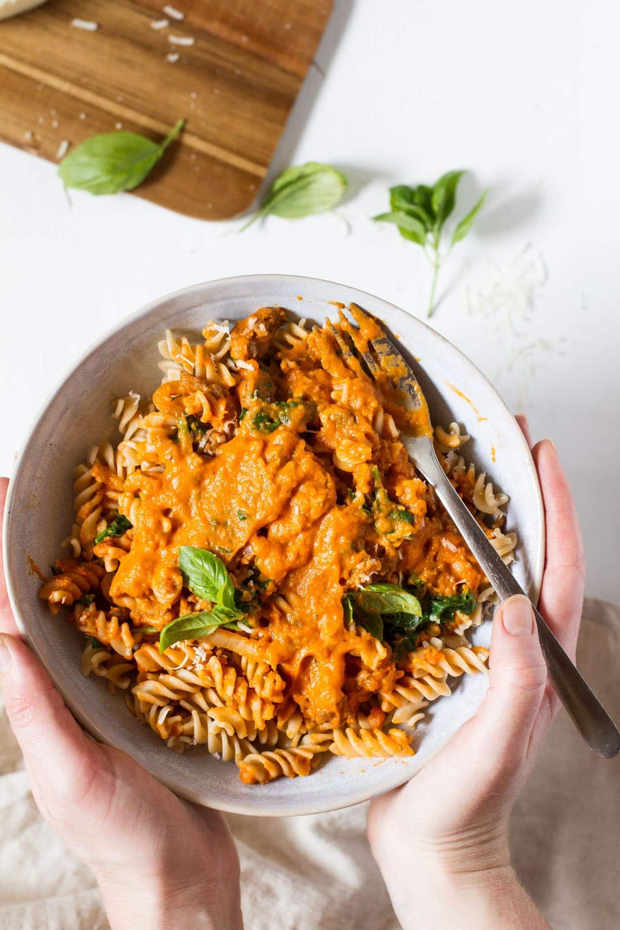 Hands holding a bowl of Creamy Parmesan Pumpkin Pasta
