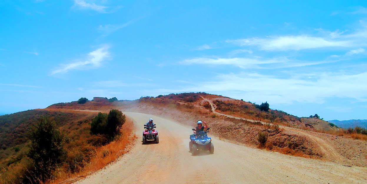 two quads riding at high speed down the hill blue skies and lots of dust