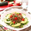 cold lentil salad with avacado slices and cherry tomatoes on a white plate