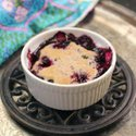 a small blueberry cobbler baked in a white dish on a trivet placed on top of a silver tray.