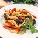 a white plate with penne pasta and roasted broccoli, carrots, and tomatoes on top.
