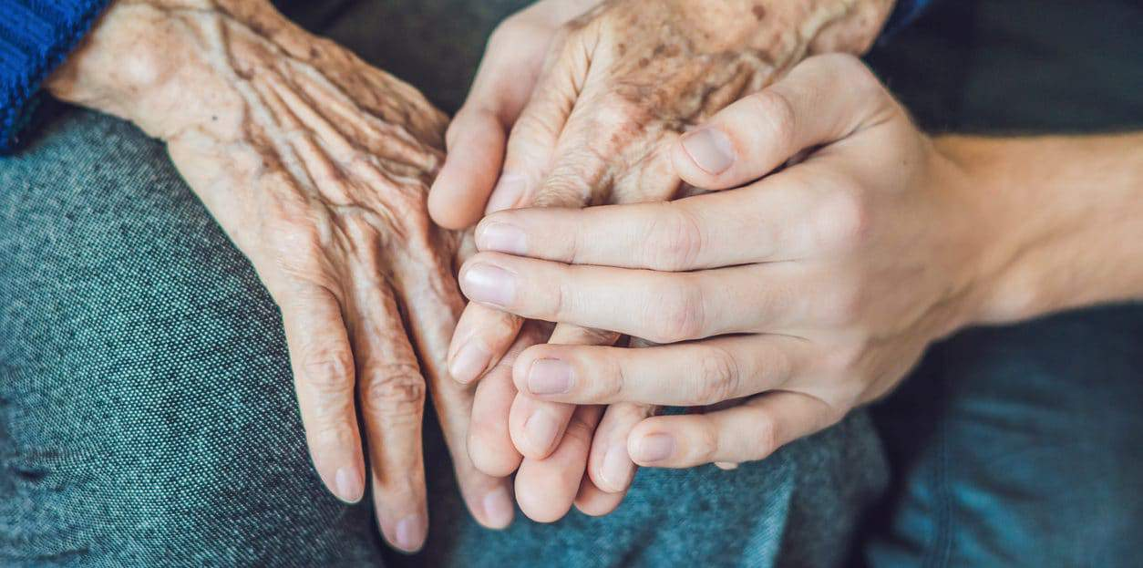 Hands of an old woman and a young man close up.