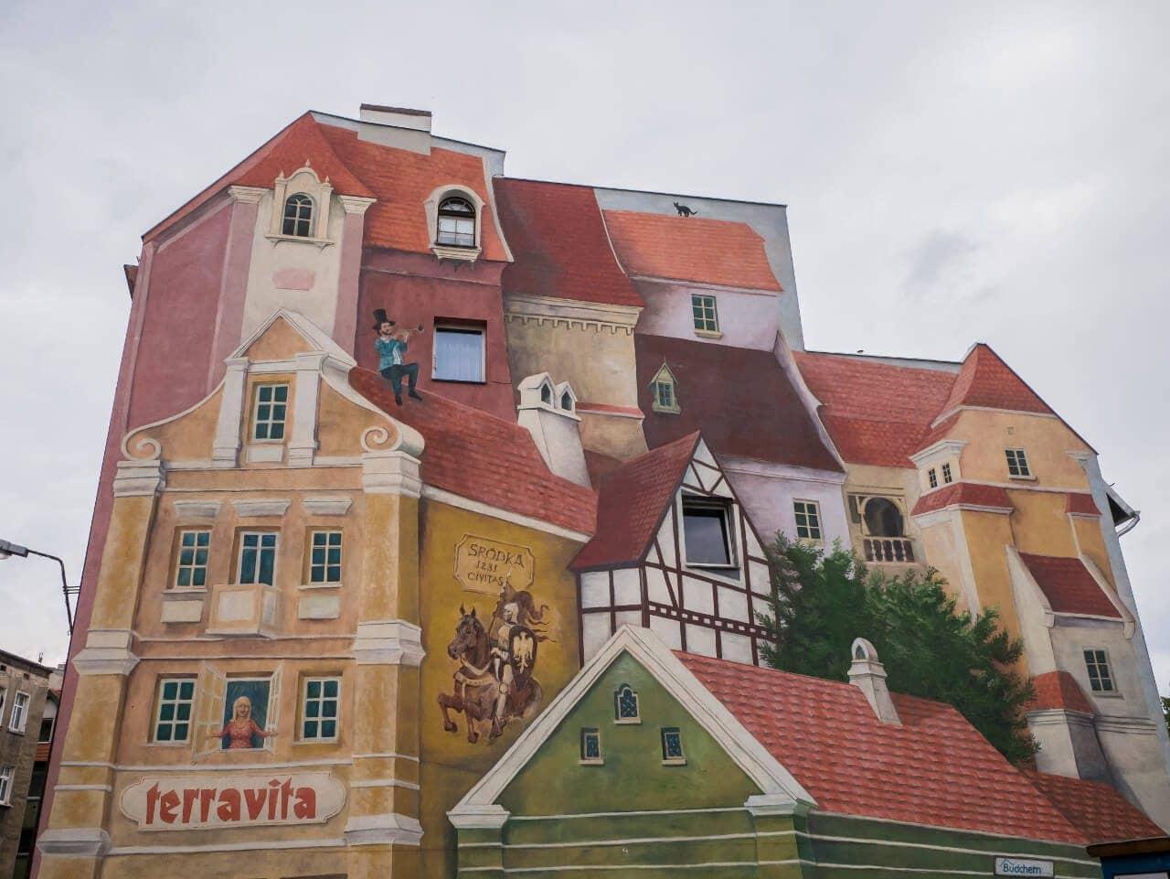 """Zbliżenie na mural """"Opowieść śródecka z trębaczem na dachu i kotem w tle"""""""