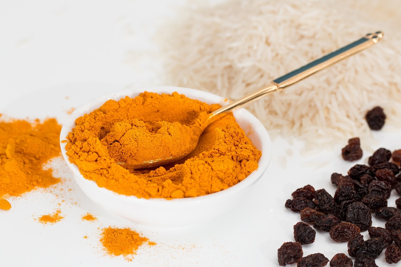 Turmeric Is it the Wonder Drug for Arthritis? - small bowl with turmeric powder and a spoon