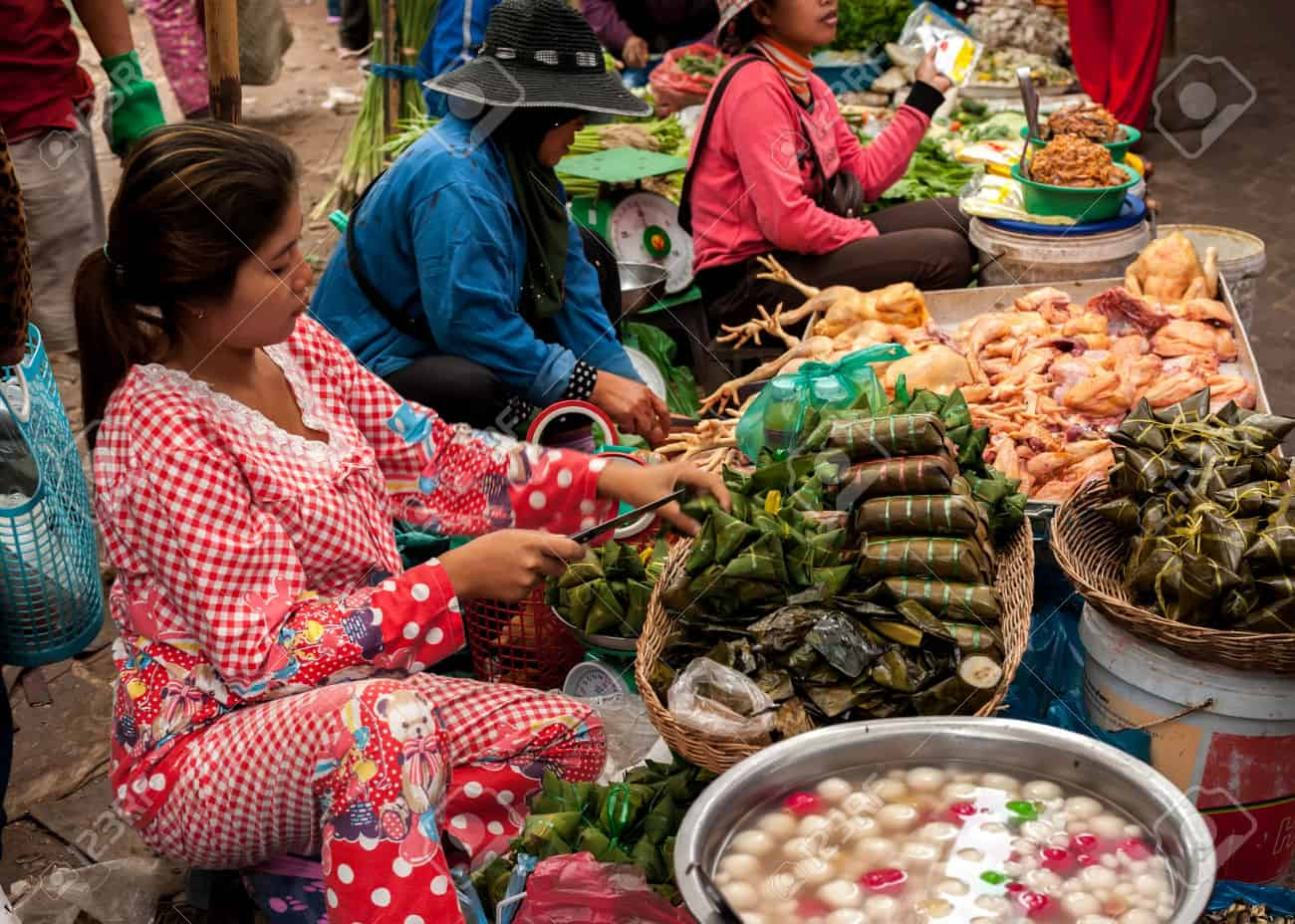 """Thai desserts wrapped in banana leaves Traditional Thai sweet food, steamed rice dough with sweet coconut stuffing in banana leaf . also called """"ka-nom-sai-sa i"""" on wicker basket in culture market at Thailand"""