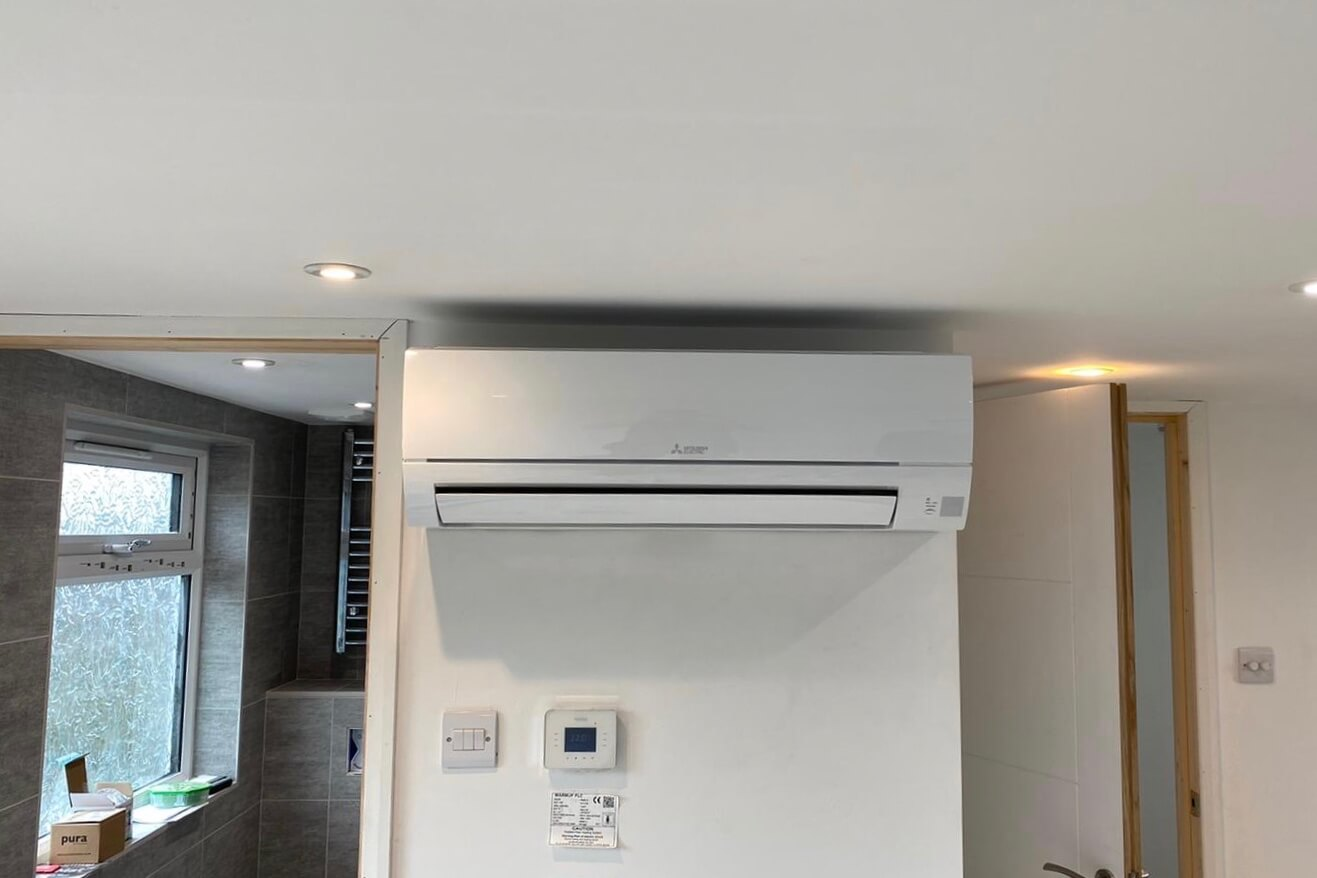Littlehampton, West Sussex loft conversion with white Mitsubishi Electric wall-mounted air con unit inside by bathroom straight on SubCoolFM