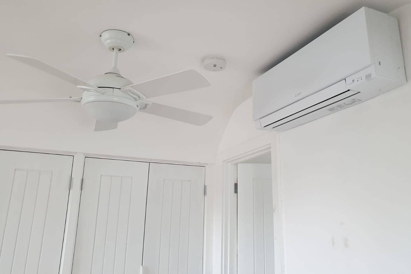 White wall mounted mitsubishi electric zen air conditioning unit in white room next to ceiling fan and cupboards