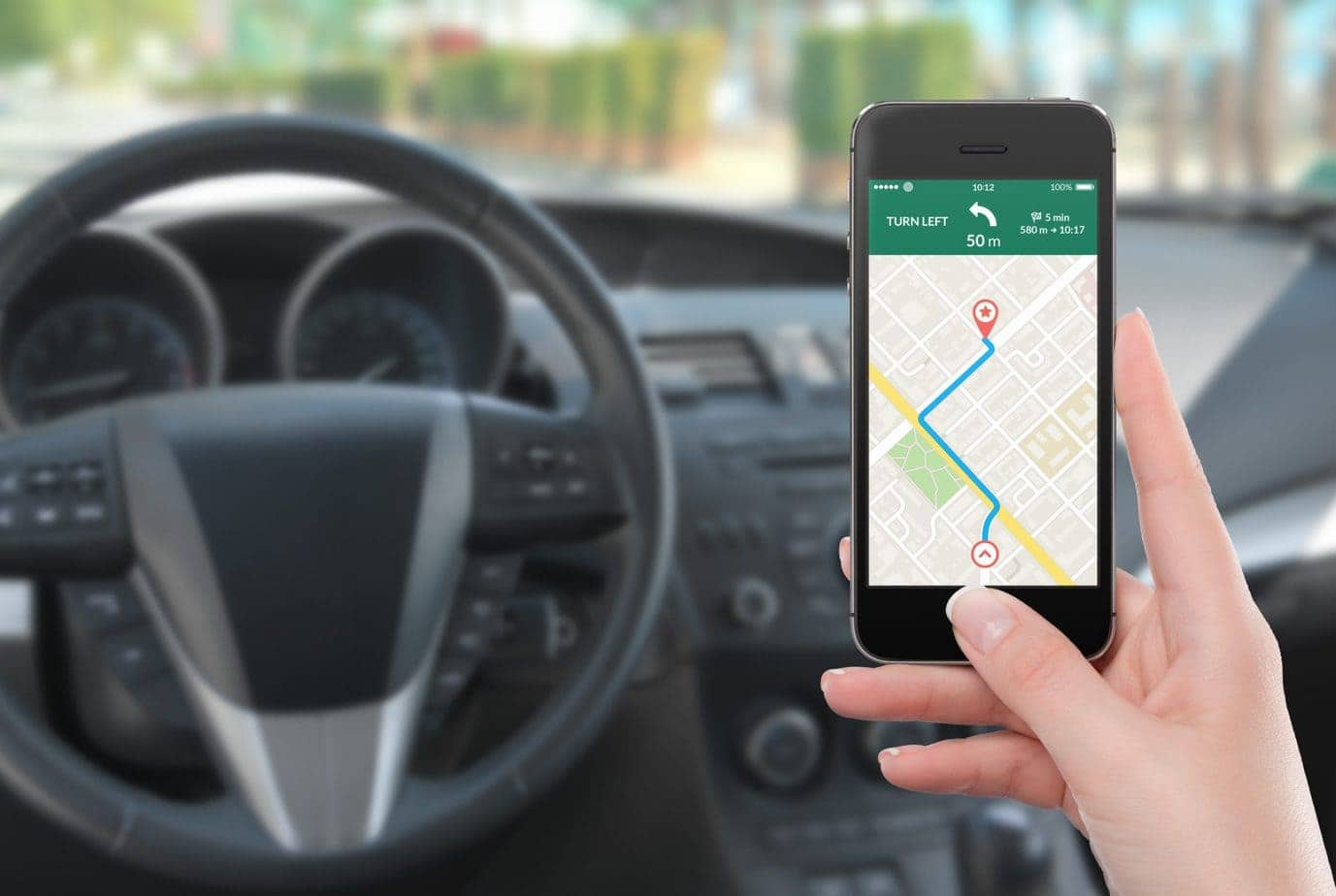 car driver holding mobile phone looking at navigation app