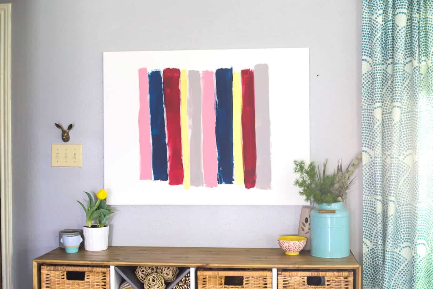 Canvas brush stroke art hanging on a wall above a wooden credenza
