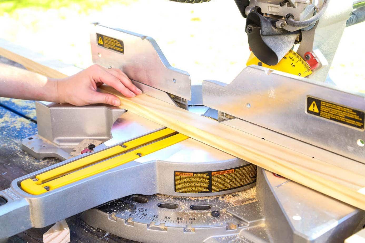 Close up of woman cutting wood using a miter saw