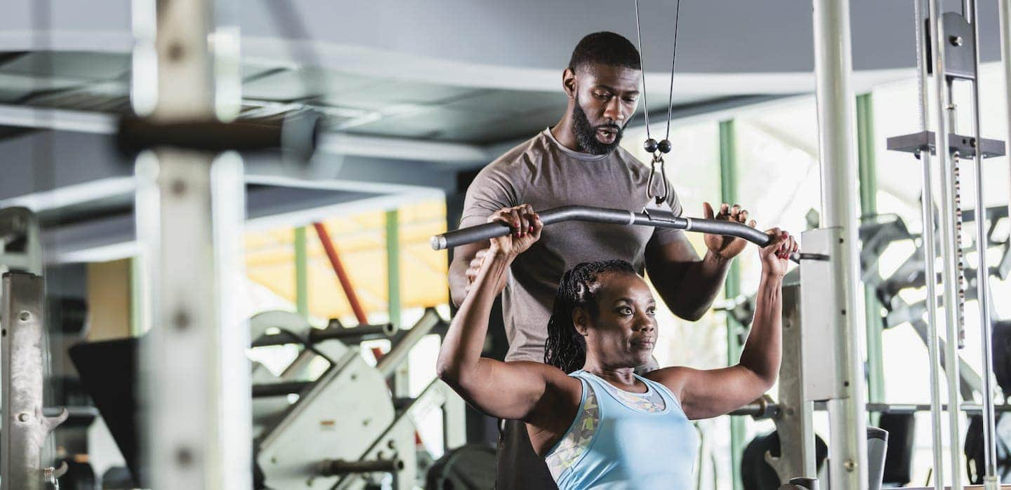 Personal trainer helping client at gym