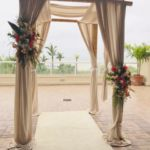 Tropical flowers set up on an arch for an outdoor wedding. Flowers by Marco Island Florist.