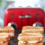 Grilled sandwiches on a griddle with a red toaster in the background.