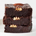 Stack of 3 fudgy coconut flour brownies with pecans