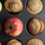 Apple cider muffins in muffin tin with apple