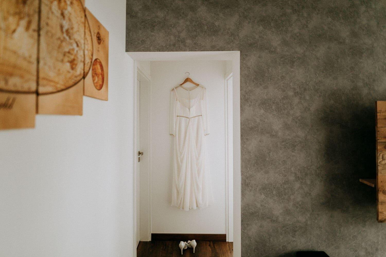 suknia slubna wisi na drzwiach w domu pani mlodej