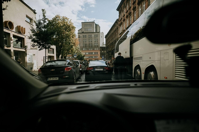 para mloda jedzie autem do kosciola ulicami krakowa
