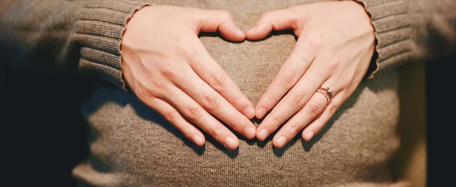 Pregnant woman making a heart with her hand