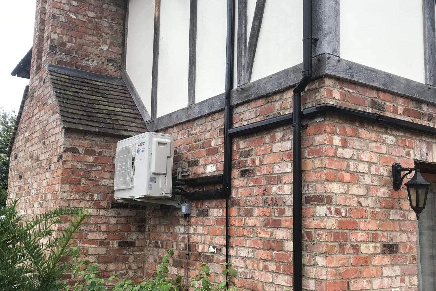 Exterior wall mounted mitsubishi electric domestic air conditioning unit neatly fitted by SubCool FM side view