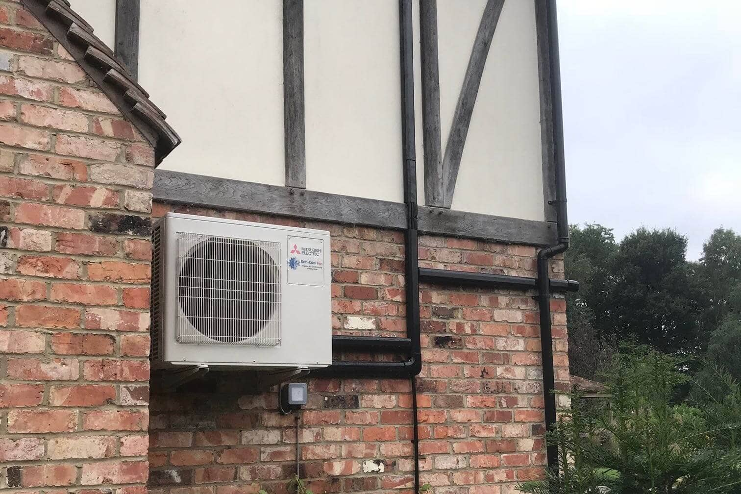 Exterior wall mounted mitsubishi electric domestic air conditioning unit neatly fitted by SubCool FM